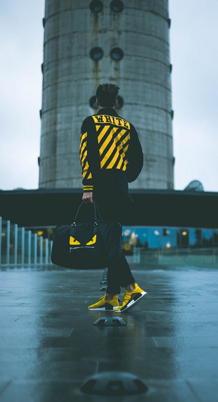 An off-white model wears clothes and sneakers
